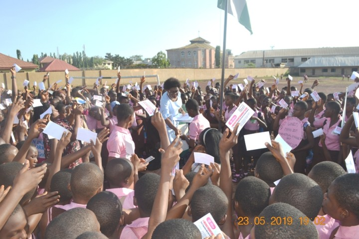 Executive Director WINET Miriam Menkiti giving Menstral Hygiene Day stickers to students of Girls High School Uwani Enugu, Enugu State Nigeria